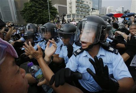 Police try to hold back pro-democracy student protesters during a scuffle as an ambulance tries to leave the compound of the chief executive office in Hong Kong, Friday, Oct. 3, 2014. Hong Kong protesters on Friday welcomed an overnight offer by the territory's leader of talks to defuse the crisis over demonstrations seeking democratic reforms, though they continued to demand he resign and maintained barricades around government headquarters, frustrating staff going to work.