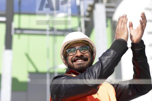 Portrait of happy construction engineer in front of power station wearing hard hat and safety vest clapping hands