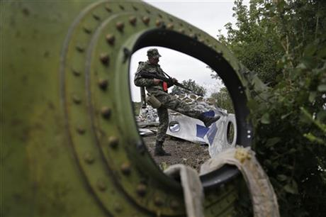 A Pro-Russian rebel looks at pieces of the Malaysia Airlines Flight 17 plane near village of Rozsypne, eastern Ukraine, Tuesday, Sept. 9, 2014.