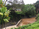 Water is seen rushing through a spillway in a neighborhood below the Nuuanu Dam in Honolulu on Thursday, Sept. 13, 2018. Honolulu officials say they may need to evacuate 10,000 people from a residential neighborhood if water in the reservoir continues to rise after heavy rains from a tropical storm. (AP Photo/Caleb Jones)