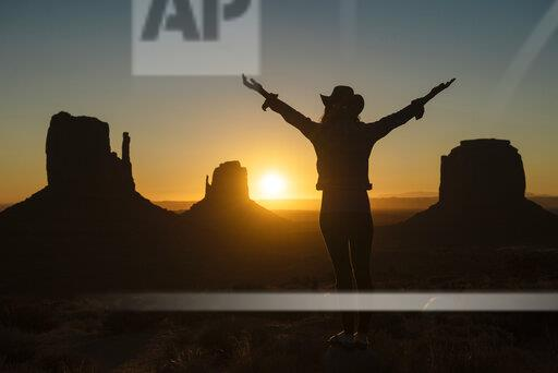 USA, Utah, Monument Valley, silhouette of happy woman with cowboy hat enjoying sunrise