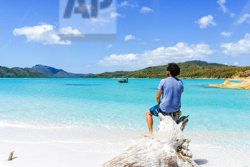 Australia, Queensland, Whitsunday Island, man sitting on log at Whitehaven Beach
