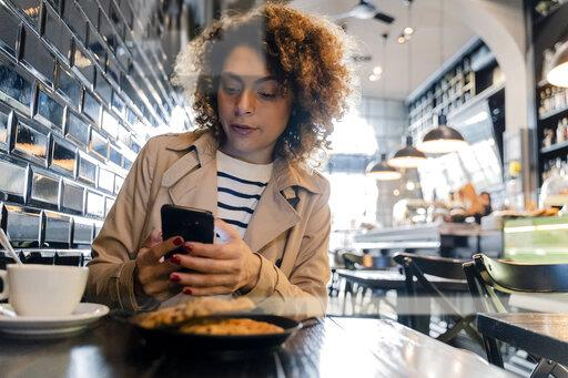 Woman using cell phone in a cafe