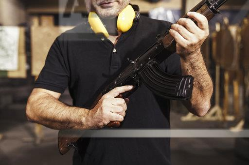 Close-up of man holding a rifle in an indoor shooting range