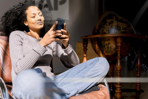 Woman sitting relaxed in armchair, using smartphone
