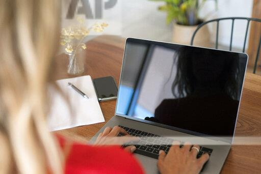 Close-up of woman using laptop on wooden table at home