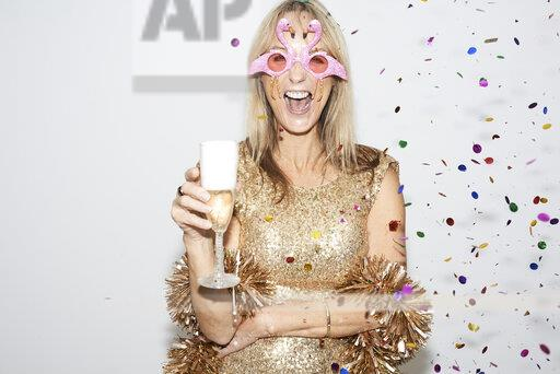 Senior woman wearing golden dress and flmingo shaped glasses, celebtraing New Year's Eve