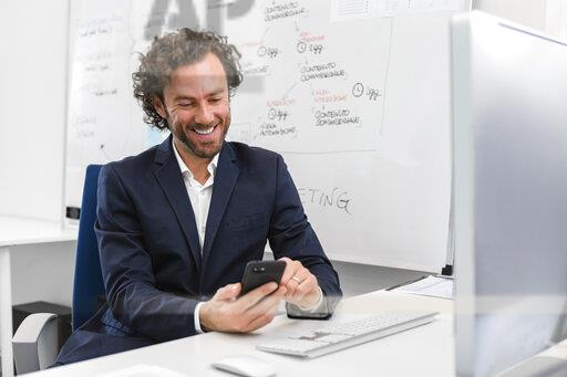 Smiling businessman sitting at desk in office using cell phone