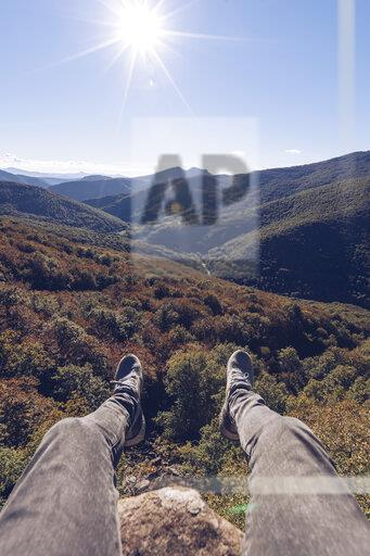 Spain, Navarra, Irati Forest, man's legs dangling above forest landscape in backlight