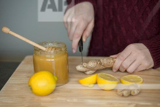 Hands of young woman cutting ginger root on wooden board
