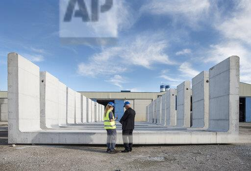 Businessman talking with female worker on industrial site in front of concrete blocks