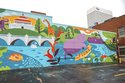 In this photo taken Wednesday, Aug. 15, 2018, the ArtWorks Cincinnati Paint by Numbers program has completed a mural of Cincinnati Zoo hippos Fiona and Bibi at the corner of Ninth and Race streets in Cincinnati. The mural was designed by Lucie Rice. (Phil Didion/The Cincinnati Enquirer via AP)