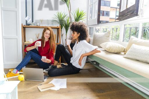Casual businesswomen sitting on floor, drinking coffee, working on laptop