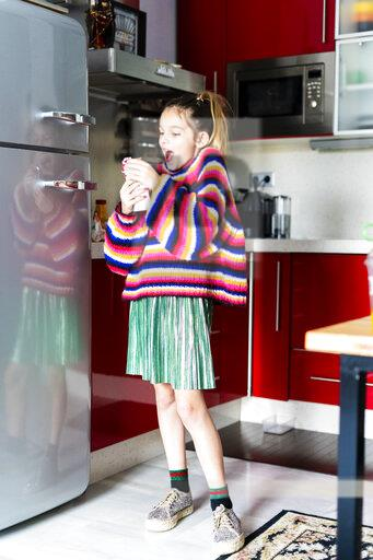 Excited girl in striped pullover in kitchen at home eating chocolate