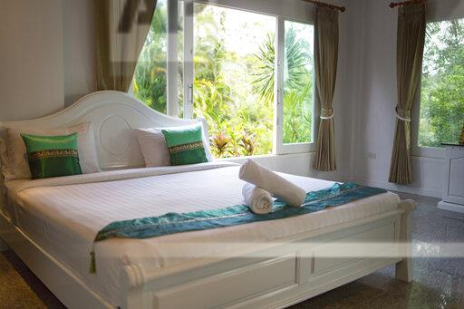 Thailand, spacious bedroom with double bed in luxury hotel