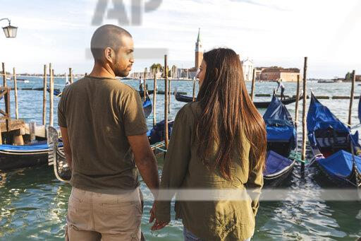 Italy, Venice, affectionate young couple with gondola boats in background