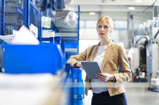 Businesswoman with tablet in factory storehouse