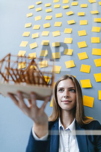 Young businesswoman holding architectural model with yellow sticky notes on the wall behind ger