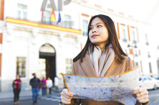 Spain, Madrid, young woman with map exploring the city