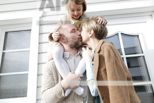 Happy family hugging and kissing in front of their house