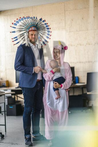 Man and woman, dressed as Indian and unicorn, standing in office, woman holding baby in her arms