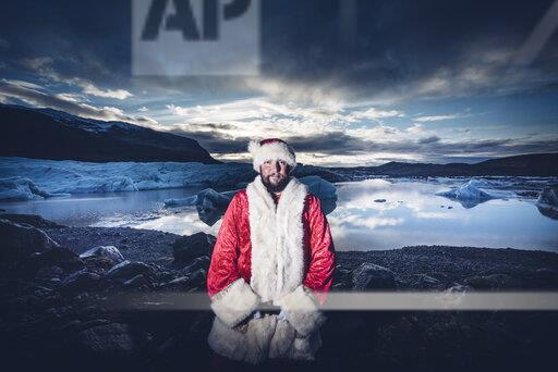 Iceland, portrait of Santa Claus standing in front of glacier
