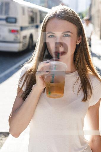 Young woman exploring New York City, drinking take-out coffee