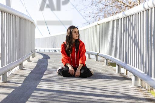 Young contemporary dancer sitting on a footbridge