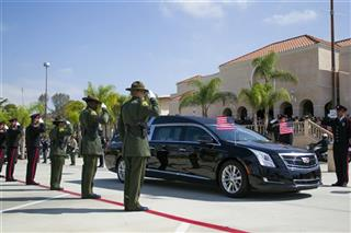 The honor guard salutes the hearse carrying the body of Officer Jonathan De Guzman.