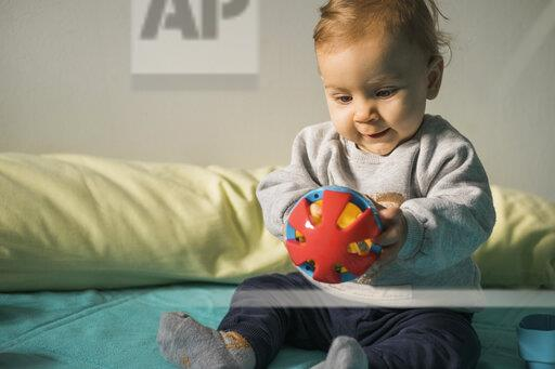 Baby girl sitting on bed playing with plastic ball