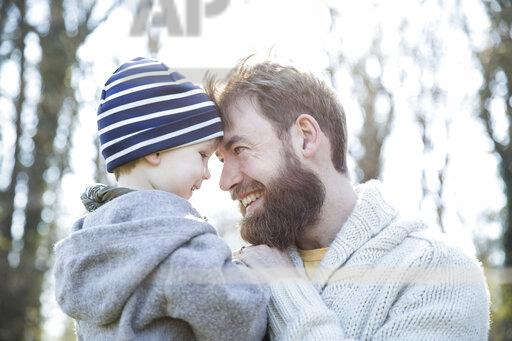 Happy father carrying son in park