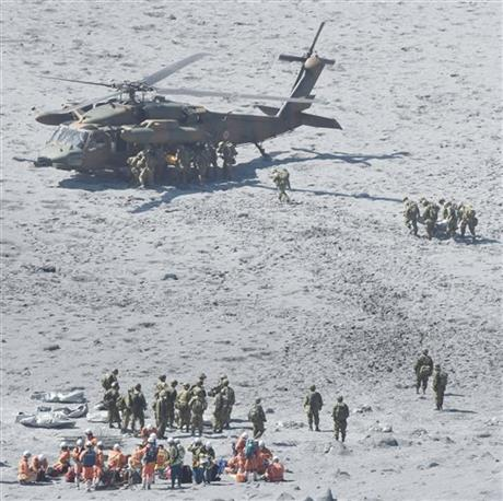 Rescuers conduct a search operation near the peak of Mount Ontake in central Japan Wednesday, Oct. 1, 2014. Search efforts for people missing since Saturday's surprise eruption resumed Wednesday morning. (AP Photo/Kyodo News) JAPAN OUT, MANDATORY CREDIT