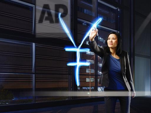 Asian businesswoman painting Yen sign with light