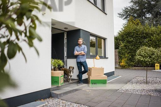 Man with dog standing at house entrance surrounded by cardboard boxes