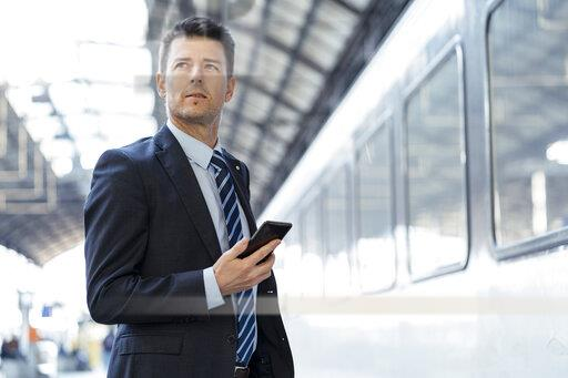 Businessman with cell phone on station platform