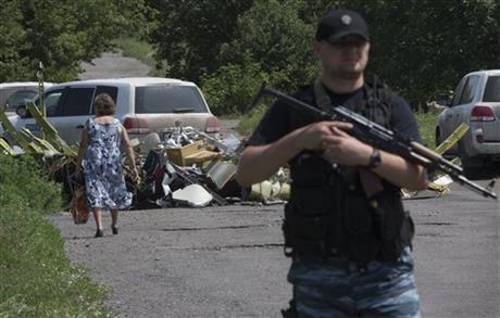 A police officer stands guard as a woman walks past pieces of the crashed Malaysia Airlines Flight 17 in the village of Petropavlivka, Donetsk region, eastern Ukraine Friday, July 25, 2014. (AP Photo/Dmitry Lovetsky)