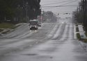 A few cars drive along an almost deserted Market St. in Wilmington, N.C., Thursday, Sept. 13, 2018. Florence's outer bands of wind and rain began lashing North Carolina on Thursday. (Matt Born/The Star-News via AP)
