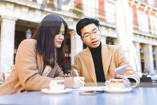 Spain, Madrid, young couple using cell phone and taking notes in a cafe at Plaza Mayor