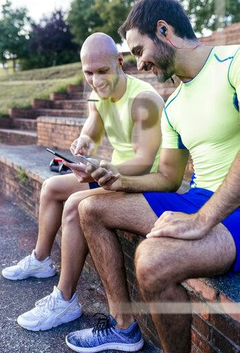 Two smiling athletes sharing smartphones after workout