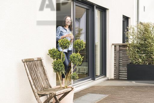 Smiling woman standing at terrace door at home with healthy drink