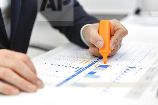 Close-up of businessman using highlighter on a report at desk in office