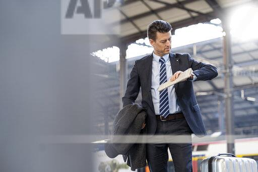 Businessman checking the time at train station