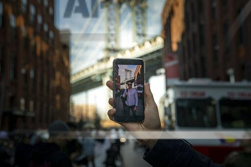 A man displays his recently captured portrait below the Manhattan Bridge in Brooklyn, New York