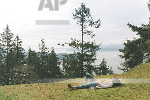 Woman relaxing in nature, lying on grass