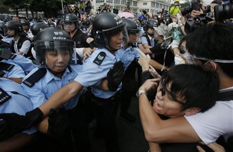 Pro-democracy student protesters scuffle with police as an ambulance tries to leave the compound of the chief executive office in Hong Kong, Friday, Oct. 3, 2014. Hong Kong protesters on Friday welcomed an overnight offer by the territory's leader of talks to defuse the crisis over demonstrations seeking democratic reforms, though they continued to demand he resign and maintained barricades around government headquarters, frustrating staff going to work.