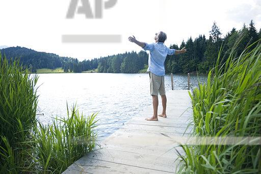 Germany, Mittenwald, mature man standing with arms outstretched on jetty at lake