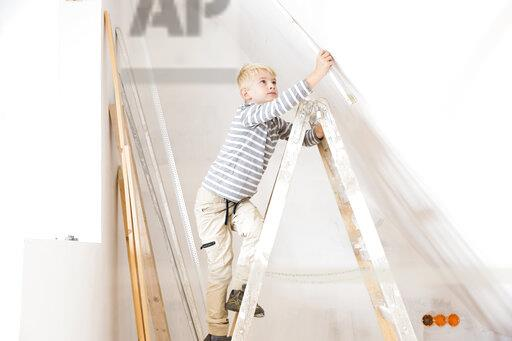 Boy with pocket rule on ladder measuring wall in attic to be renovated