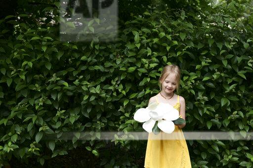 Smiling little girl with oversized white magnolia blossom