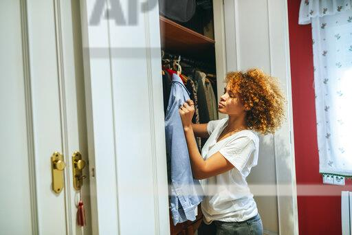 Young woman with curly hair at home looking at clothing in her wardrobe