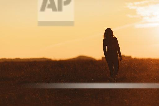 Woman walking in nature at sunset